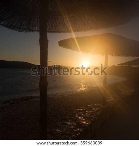 Photo closeup with sun spot of seascape with beach umbrellas for sun protection in line at seashore silhouetted against sunset background, square picture - stock photo