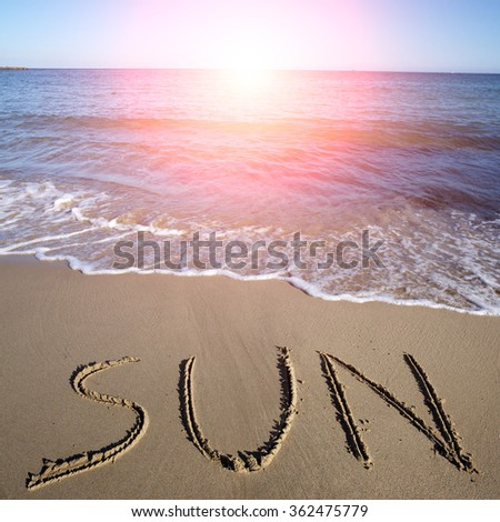 Photo closeup with sun spot of word sun written on wet beige beach sea marine grained sand against blue waves with white spindrifts running on seashore on seascape background, square picture - stock photo