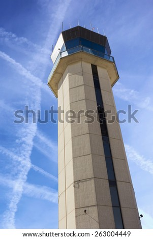 Photo composite illustration of commercial Airport Control Tower from close up perspective with sky criss crossed by jet trails illustrating air traffic control challenges. - stock photo