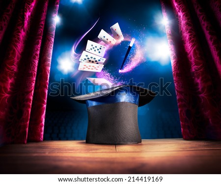 photo composite of a magic hat on a stage with cards and a magic wand - stock photo