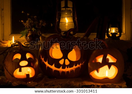 Photo composition from three pumpkins on Halloween. Crying, Jack and frightened pumpkins against an old window, dry leaves - stock photo