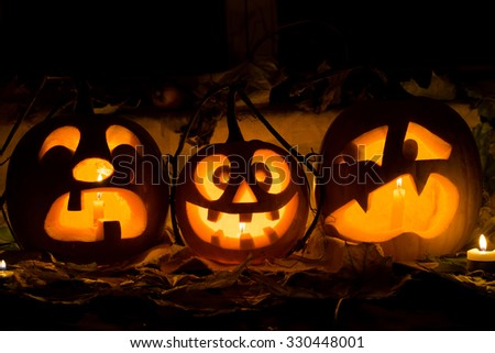 Photo composition from three pumpkins on Halloween. Crying, mad and afraid of some pumpkin against an old window, leaves and candles. - stock photo