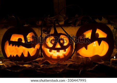 Photo composition from three pumpkins on Halloween. Embittered, mad and afraid of some pumpkin against an old window, leaves and candles. - stock photo