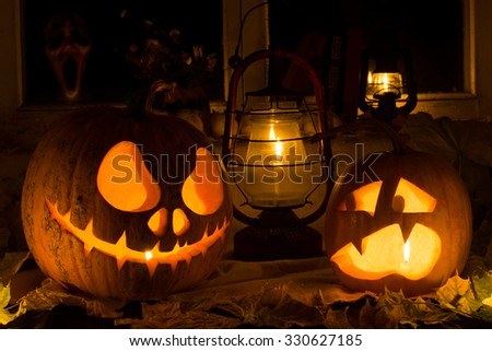 Photo composition from two pumpkins on Halloween. Jack and frightened pumpkins stand against dry leaves, candles and an old window in which the ghost looks - stock photo