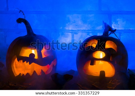 Photo composition from two pumpkins on Halloween. The embittered and crying pumpkins against a brick wall and a dense smoke - stock photo