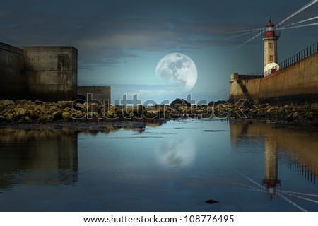 Photo composition of low tide view of lighthouse with full moon. - stock photo