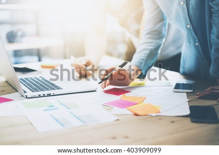 Photo coworking team meeting. Young business crew working with new startup project in studio. Modern notebook on wood table. Using marketing plans,sales reports. Horizontal, film  effect - stock photo