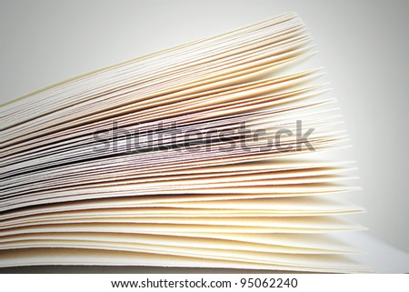 Photo detail of sheets of an open book on the grey light background