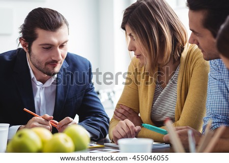 Photo editor explaining to colleagues in meeting room at creative office - stock photo