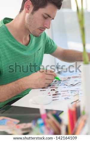 Photo editor working on a contact sheet with a green marker - stock photo