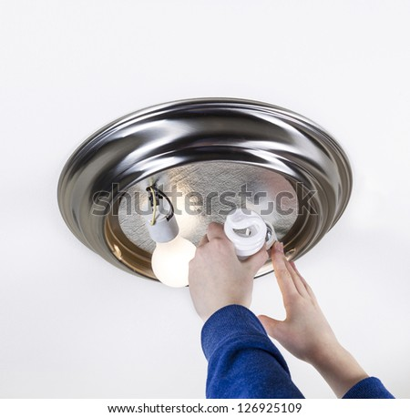 Photo female hands installing compact fluorescent bulb to replace incandescent type bulb - stock photo