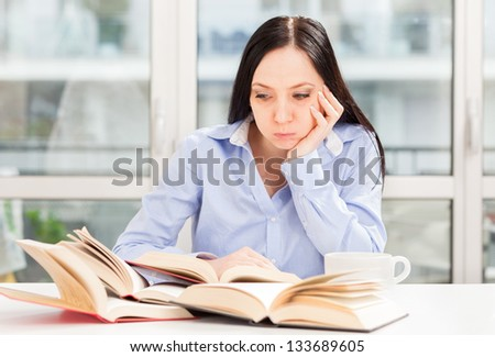 Photo Female Student learning at home with different books