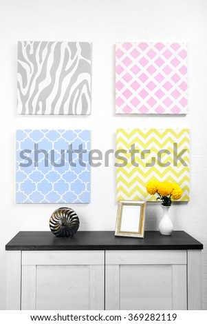 Photo frame and decorations on table with pictures in light room - stock photo