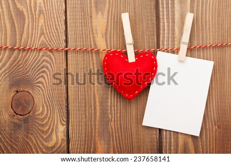 Photo frame and valentines toy heart over wooden background - stock photo