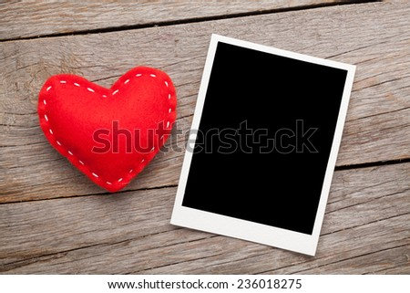 Photo frame and valentines toy heart over wooden table background - stock photo