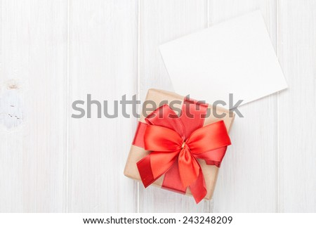 Photo frame card and gift box with ribbon over wooden table background - stock photo
