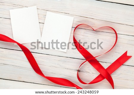 Photo frame cards with valentines heart shaped ribbon over wooden table background - stock photo