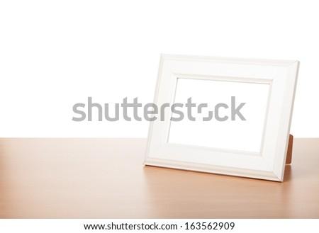 Photo frame on wood table. Isolated on white background - stock photo
