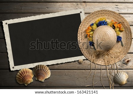 Photo Frame on Wooden Boardwalk with Sand / Aged photo frame with seashells on beach, straw hat with flowers on wooden floor with sand - stock photo