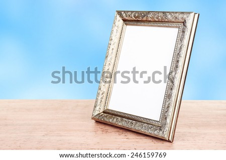 Photo frame on wooden table on blue background - stock photo