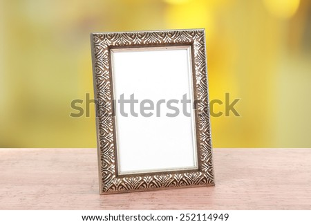 Photo frame on wooden table on bright background