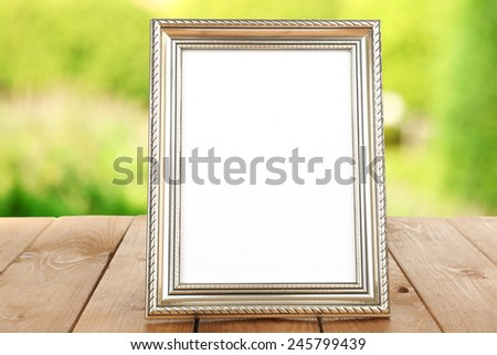 Photo frame on wooden table on nature background - stock photo