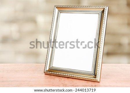 Photo frame on wooden table on wall background - stock photo