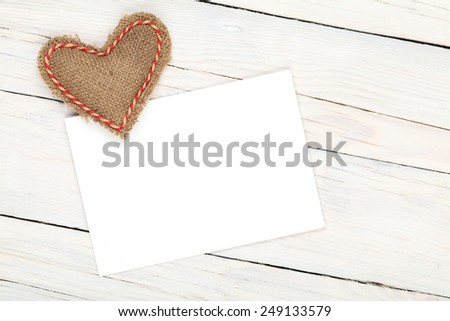 Photo frame or greeting card and handmaded valentines day toy heart over white wooden background - stock photo
