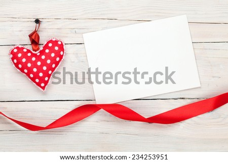 Photo frame or greeting card with valentines toy heart over wooden table background - stock photo