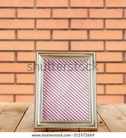 Photo frame standing on table on brick wall background - stock photo