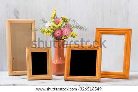 photo frames and flowers on old white table - stock photo