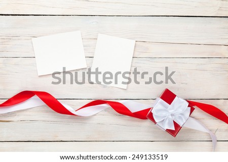 Photo frames and gift box with ribbons over white wooden table background - stock photo