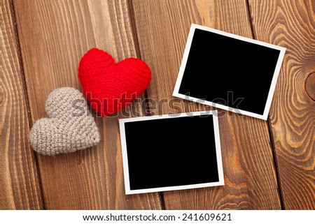 Photo frames and handmaded valentines day toy hearts over wooden background - stock photo