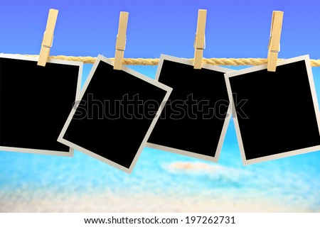 Photo frames hanging on a rope in front of the sea - stock photo