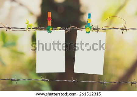 Photo Frames on barbed wire with colored clothespins,vintage effect - stock photo