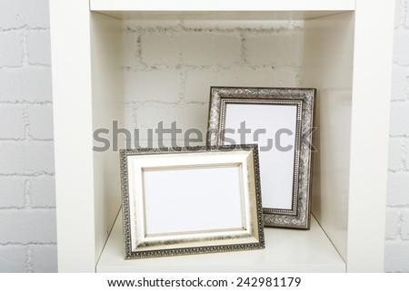 Photo frames on shelf on brick wall background - stock photo