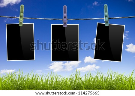 Photo frames pictures on blue sky and grass background - stock photo