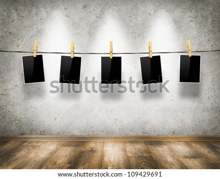 Photo frames with pins on rope over old aged wall and wood floor background - stock photo