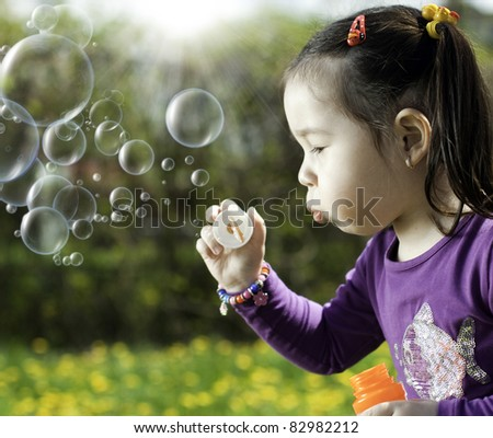 Photo girls play with soap bubbles under the bright sun