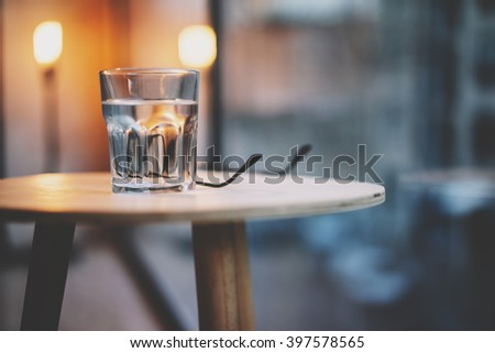 Photo glass water modern loft interior wood table. Restaurant nobody.   Horizontal, blurred background, bokeh, film effect.