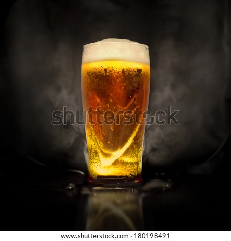 Photo glasses of beer with backlight and smoke - stock photo