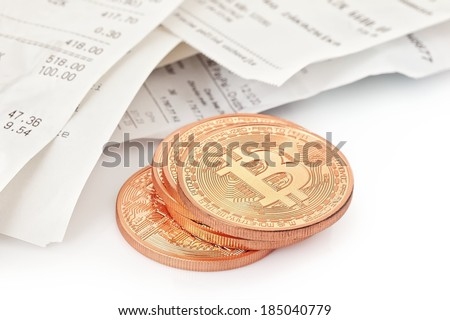 Photo .Golden Bitcoins (new virtual money ) and paper cash register receipts - stock photo