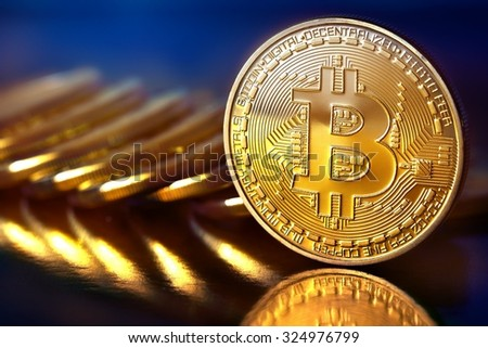 Photo Golden Bitcoins (new virtual money ) Close-up on a blue background. - stock photo