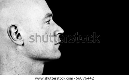 photo high contrast dark moody close up picture of a male head from side on black - stock photo