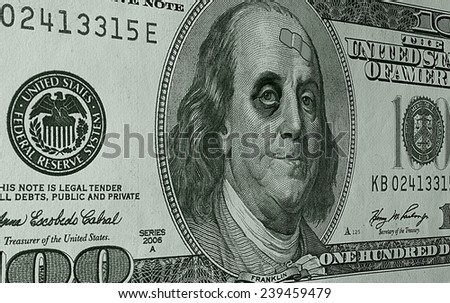 Photo Illustration of Ben Franklin on a hundred dollar bill, sporting a black eye and a band-aid, as the weak dollar takes a beating. - stock photo