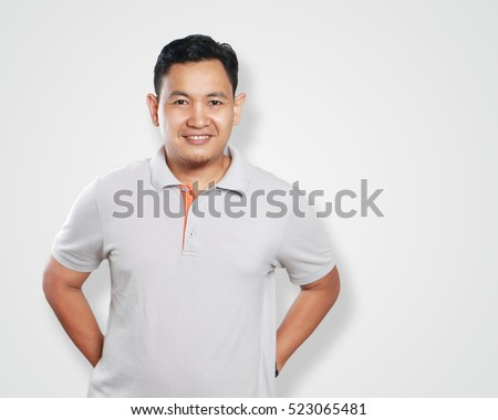 Photo image portrait of a cute handsome young Asian man smiling confidently with his arms behind his back, friendly gesture