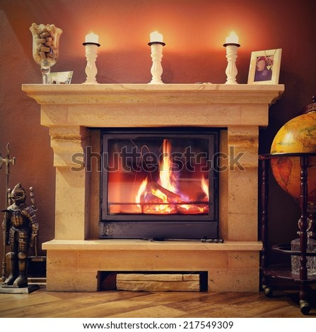 Photo interior of a home with a burning fireplace, candles and decorations. Ready for gifts for Christmas.  - stock photo