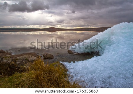 Photo lakeside spring with heaps of ice. - stock photo
