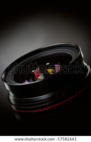 Photo lens with reflections on black background - stock photo