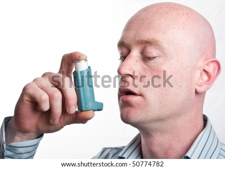 photo male man with inhaler for asthma on white backdrop isolated man inhaler. man holding a asthma inhaler putting it up to his mouth. close up of inhaler and face.